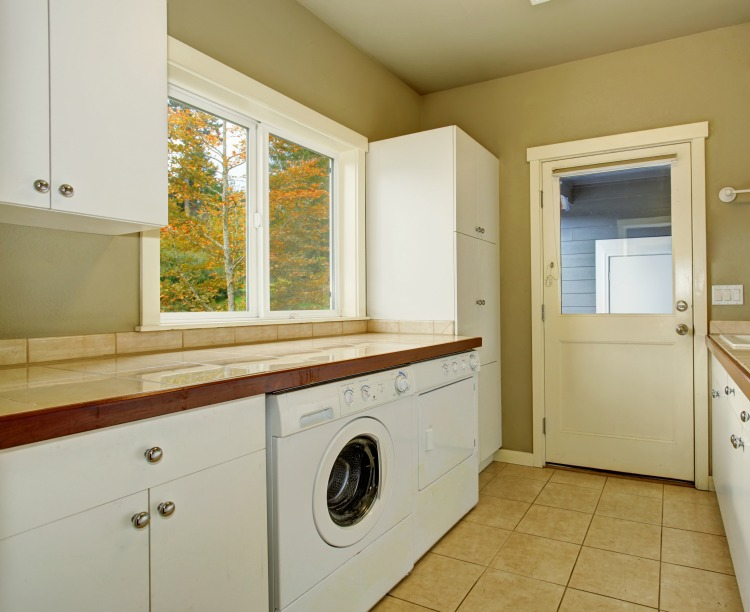 utility room with cabinets, tile counters, washer, and dryer.