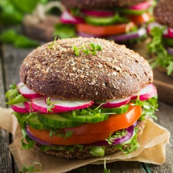 Healthy fast food. Vegan rye burger with fresh vegetables on old wooden background