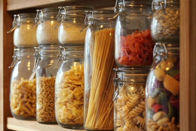 Photo of dried pasta in jars on a shelf in a domestic kitchen.  Very shallow depth of field focusing on the middle jar.
