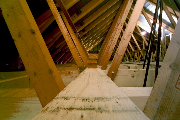 Builders building loft extension in suburban house