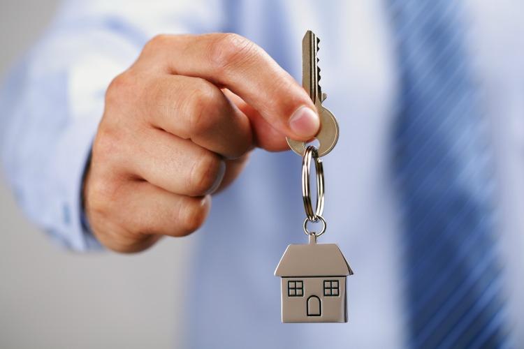 Holding out house keys on a  house shaped keychain